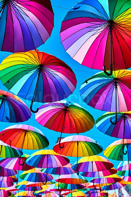 Rainbow umbrella on sky background. Many colorful umbrellas. umbrella street decoration, stock photo