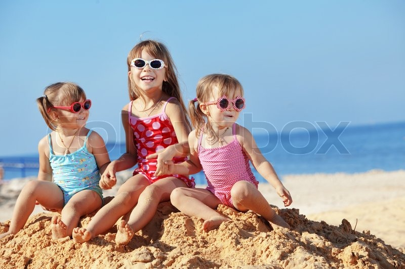 Happy kids playing at the beach in summer, stock photo