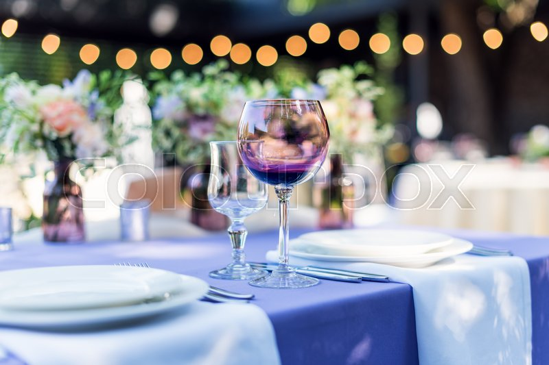 Flower table decorations for holidays and wedding dinner. Table set for holiday, event, party or wedding reception in outdoor restaurant, stock photo