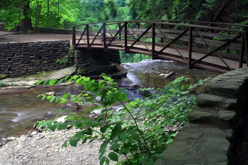 Wooden bridge over stream with small waterfall stock for Garden pond bridges sale