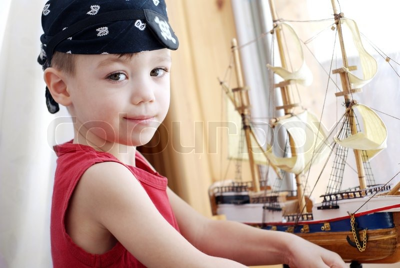 Stock image of 'Portrait of little pirate with model ship'