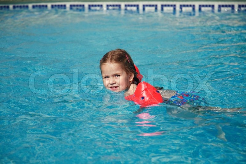 Small Girl Swimming In Pool With Water Wings Stock Photo