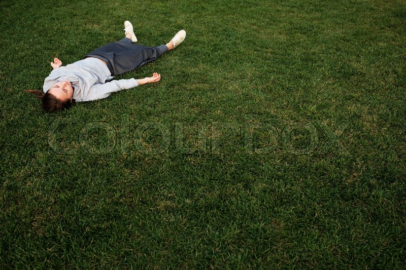 Beautiful young european woman lays down on grass and rests in summer day, stock photo