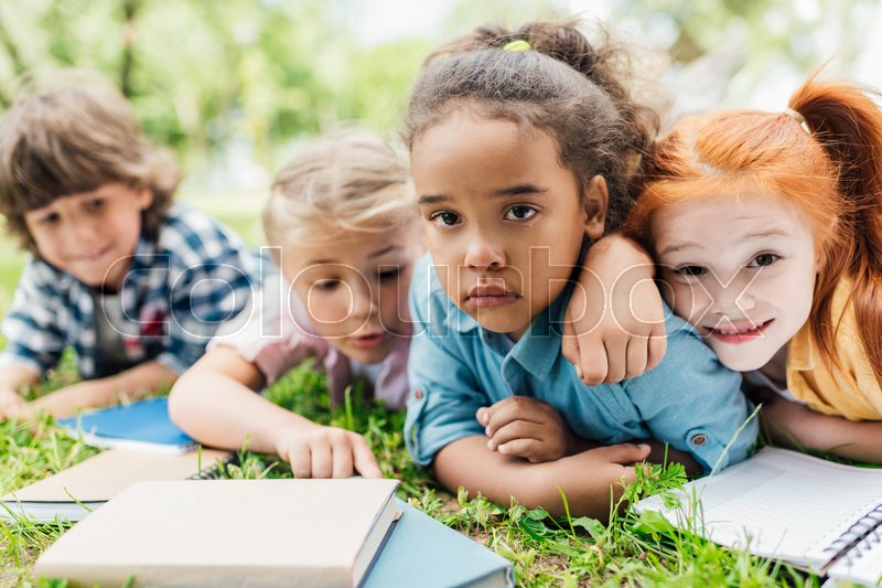 Cute multiethnic kids with books lying on grass, stock photo