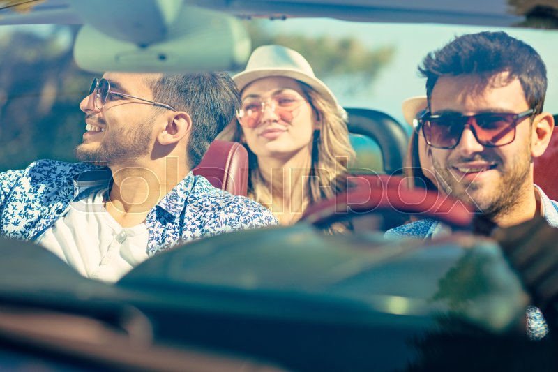 Group of cheerful young friends driving car and smiling in summer, stock photo
