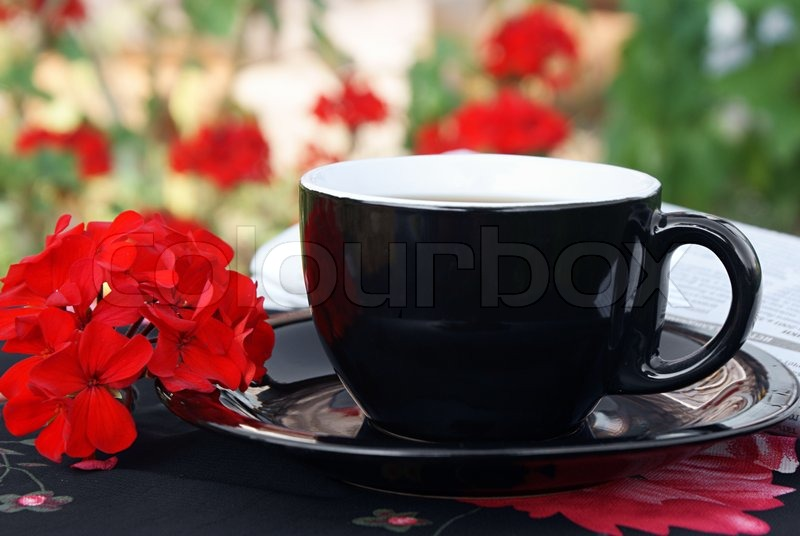 Black Cup Of Coffee With Red Flowers Stock Photo
