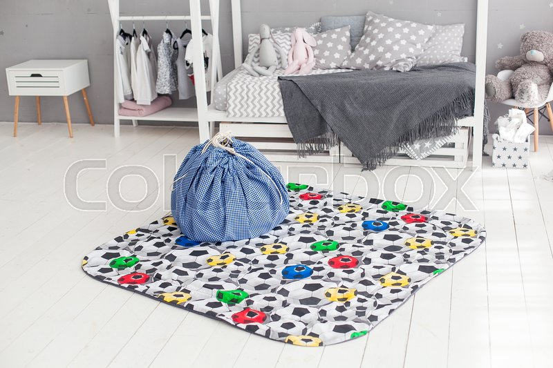Modern interior of the child\'s bedroom with carpet and bag in front. Loft grey style, stock photo