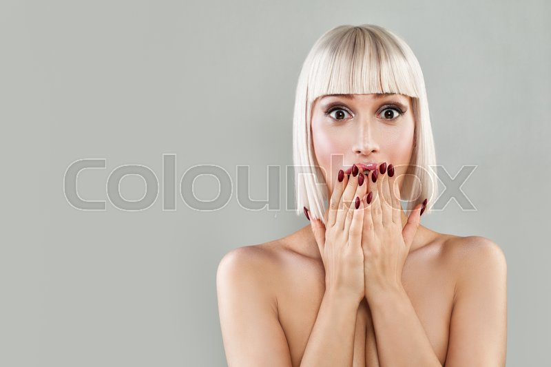 Happy Surprised Woman with Open Mouth. Blondie Model with Makeup and Bob Hairstyle on Banner Background, stock photo