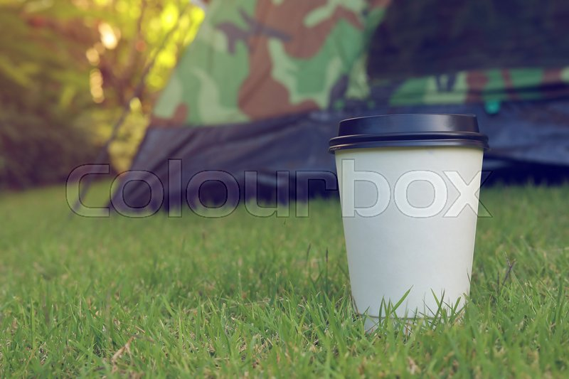 Hot coffee drink, white disposable cup on green grass lawn campsite, tent camping trip journey travel in nature, stock photo