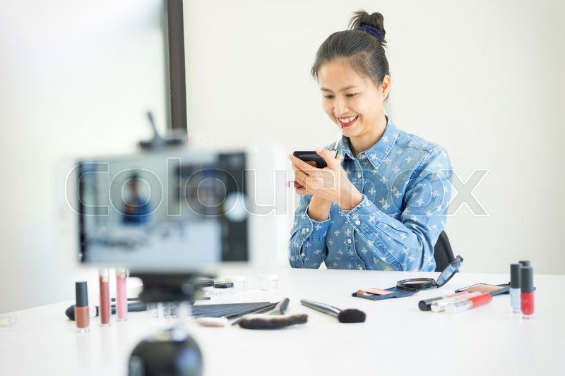 Woman present beauty cosmetic product and broadcast live video to social network by internet at home, beauty blogger concept , stock photo