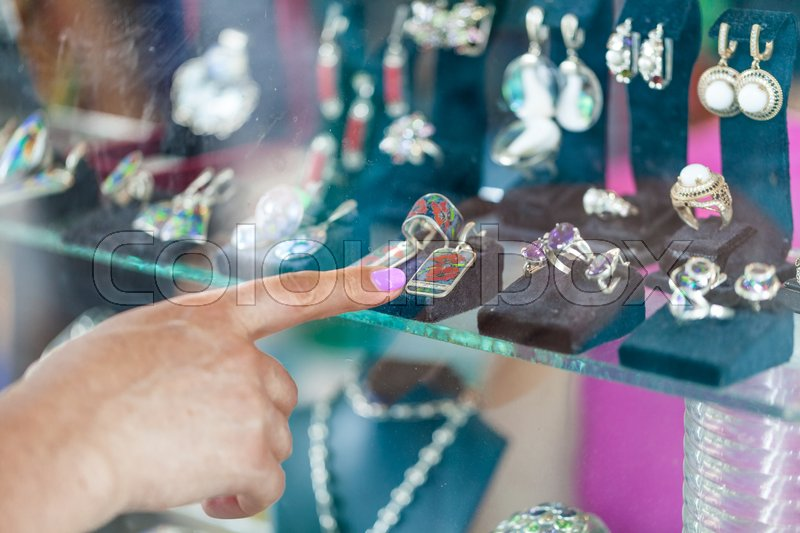 Woman looking to showcase or shop window. Shopping woman chooses jewelry in store, stock photo