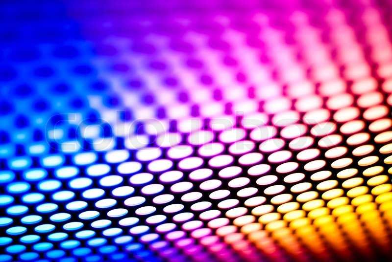 A metalic reflective surface back lit by a colorful light, stock photo