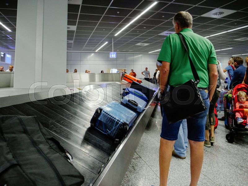 Editorial image of 'FRANKFURT, GERMANY - AUG 8, 2017: Exhausted passengers commuters waiting to claim the baggage luggage at modern airport looking at the luggage conveyor belt for their suitcase bag backpack'