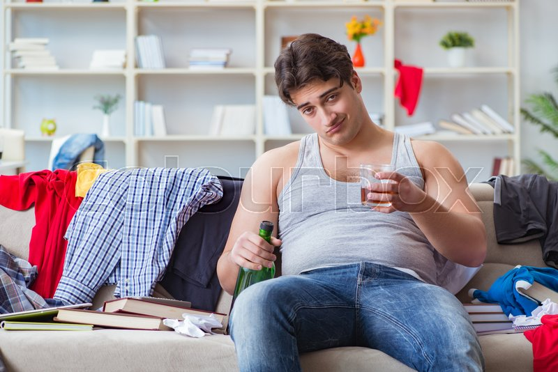 Young man student drunk drinking alcohol in a messy room, stock photo