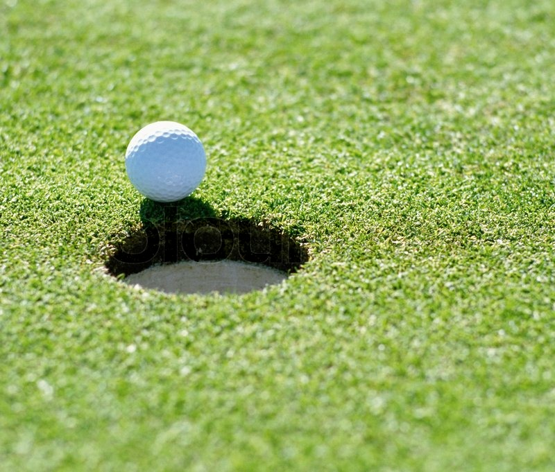 A golf ball just about to go in the hole from a long putt, stock photo