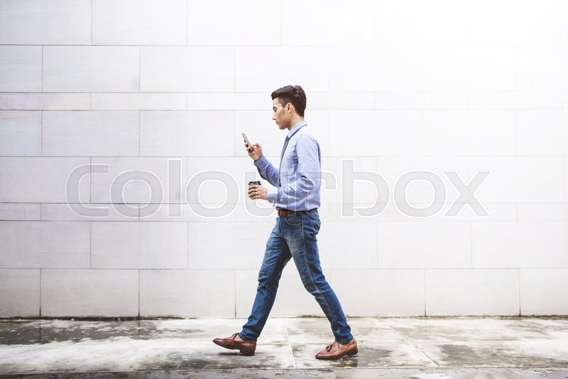 Young motivation Businessman use smart phone while walk outdoor building, Lifestyle of modern male to communicate, message or technology in business concept, stock photo