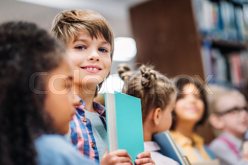 Adorable little kids with books in school library, stock photo