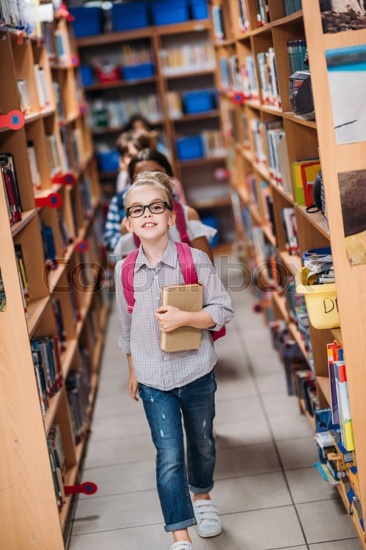 Adorable kids with books walking through library, stock photo