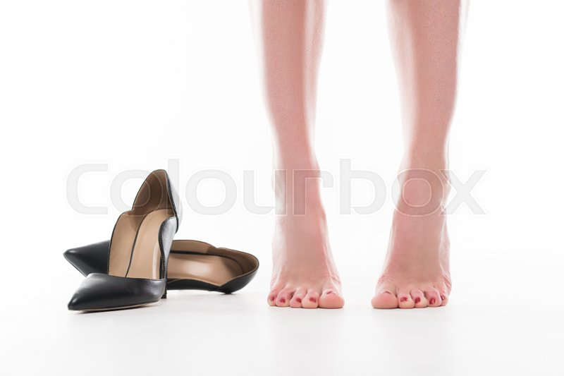 Stock image of 'cropped view of tired female legs and heels, isolated on white'