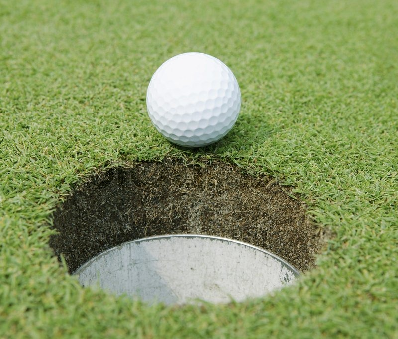 Close-up of a golf ball at the edge of the hole, stock photo