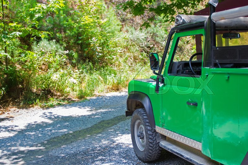Travel and summer activity concept - green safari car in forest, stock photo