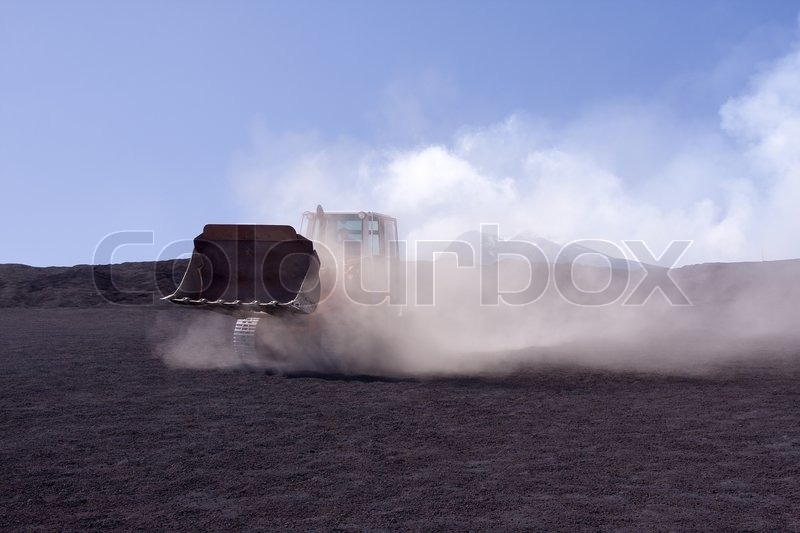 Bulldozer during work covered in dust clouds, stock photo