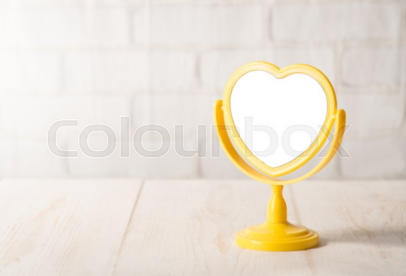 Makeup mirror in shape of heart on wooden table, Cosmetic objects, stock photo
