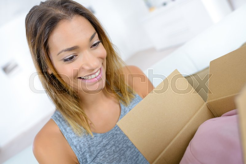 Surprised young woman opening a carton box and smiling, stock photo