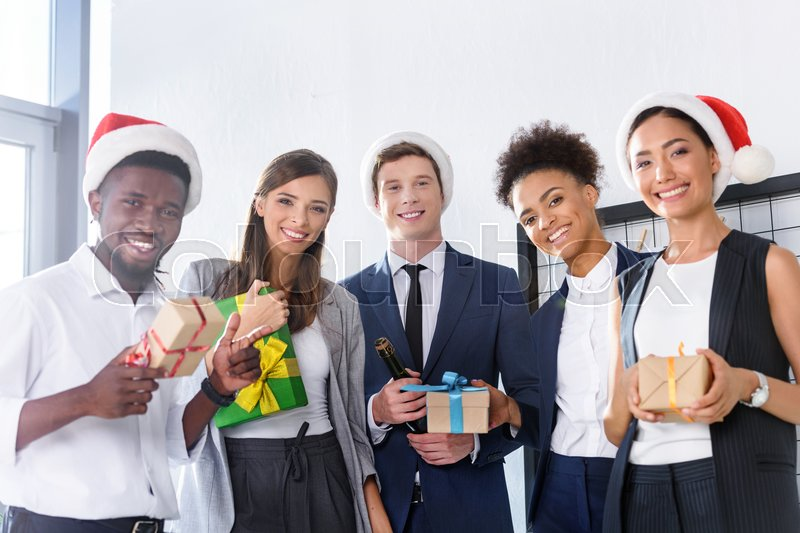 Happy young multiethnic business people holding gifts and smiling at camera in office , stock photo