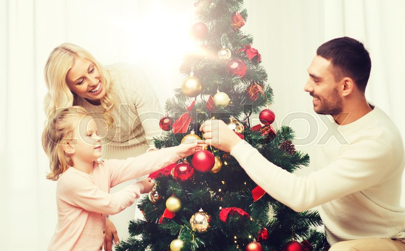 Family, x-mas, winter holidays and people concept - happy mother, father and little daughter decorating christmas tree at home, stock photo