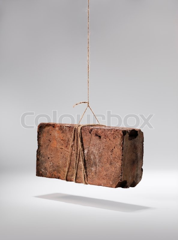 Old worn and weathered brick hanging by a piece of string Stock Photo Colourbox