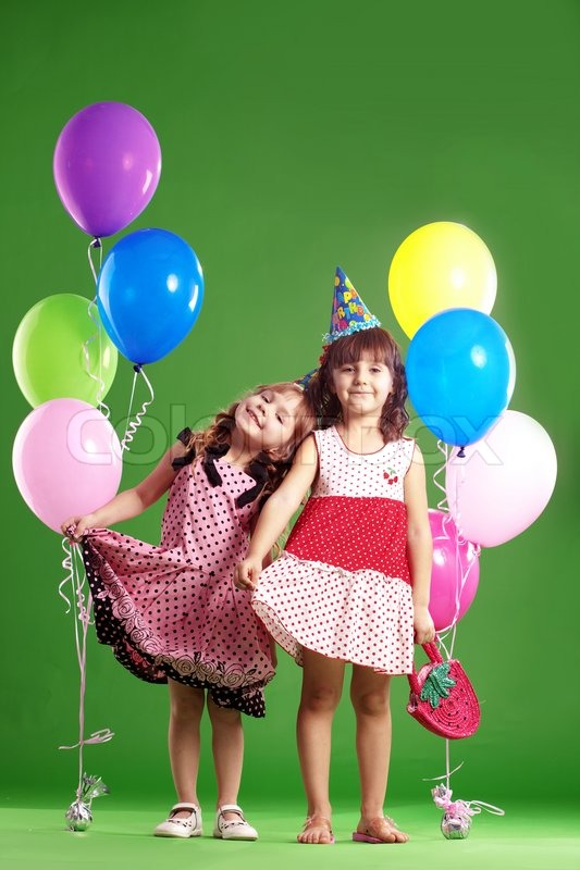 children celebrating birthday on green studio background