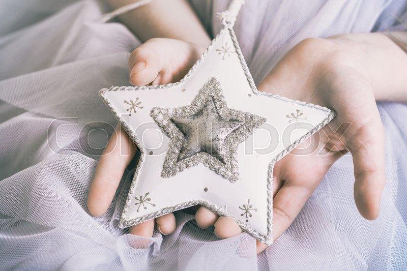 Christmas - children\'s hands girl holding a star , stock photo