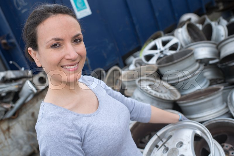 Happy mechanic woman with tyres on background, stock photo