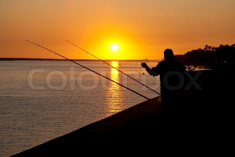 Silhouette of man fishing on sunset in a dock near the for Fishing docks near me