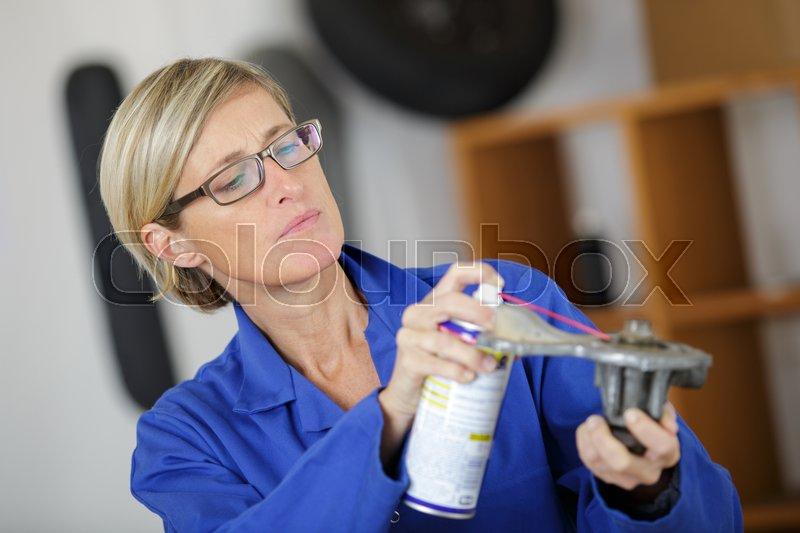 Auto mechanic woman lubricating auto part, stock photo