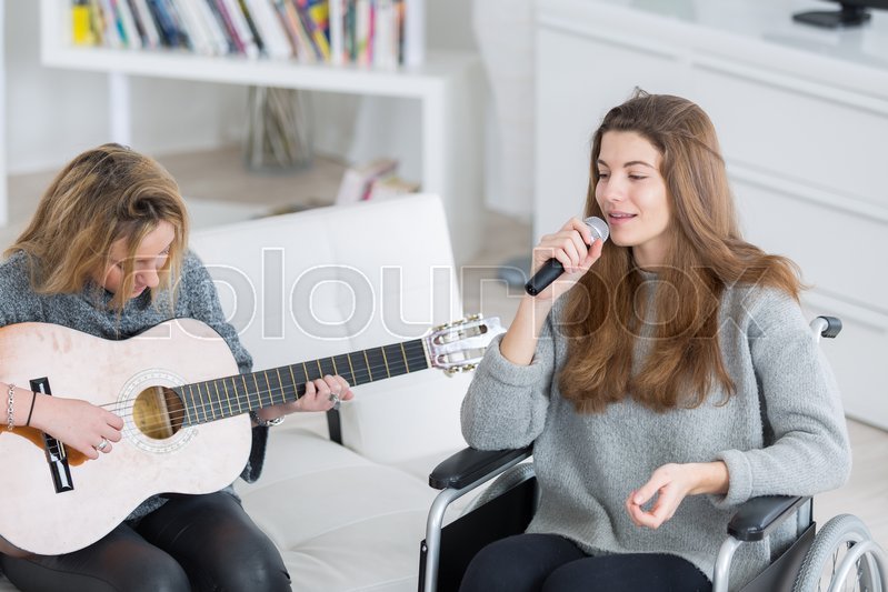 2 teen girls doing music together one is disabled | Stock Photo | Colourbox