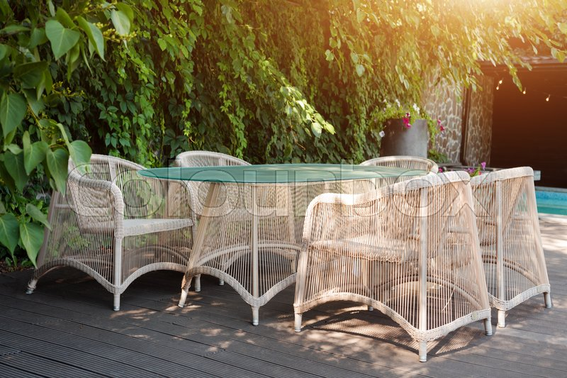 Wicker armchairs and table, modern garden furniture. Cozy space for relax in the garden, stock photo
