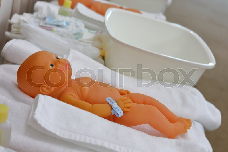 Baby doll in nursery class room with parents training child care infant, stock photo