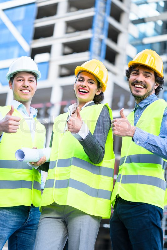 Team of civil engineers and architects at construction site giving thumbs up gesture and saying OK, stock photo