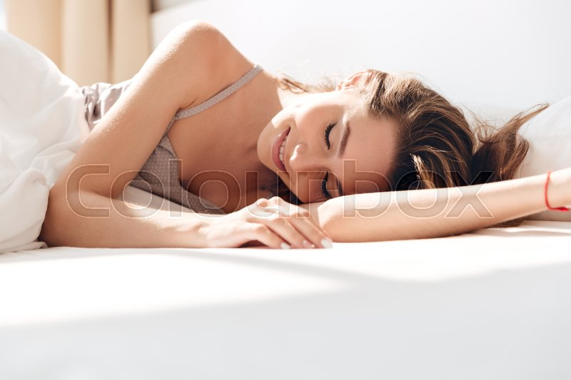 Pretty young brunette woman in pajamas sleep in bed in the morning, stock photo
