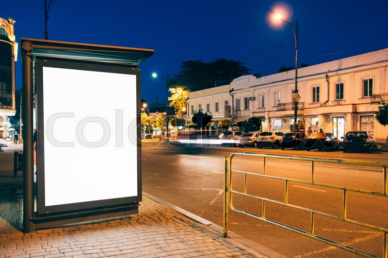 Blank advertising display at a bus stop in the city at night, stock photo