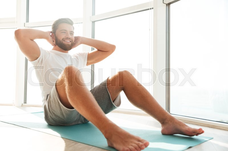 Smiling Handsome bearded man doing abdominal exercises near the window at home, stock photo