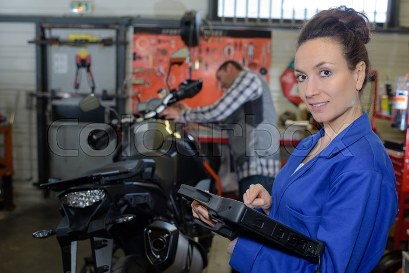 Brunette woman mechanic repairing a motorcycle in the workshop, stock photo