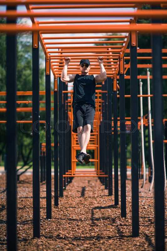 Selective focus of serious man exercising on sports ground, stock photo