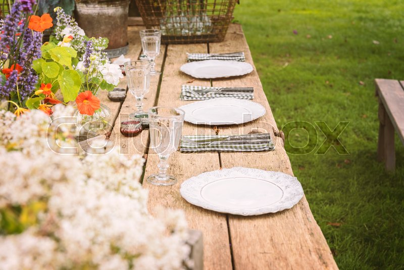 Wooden table setup for garden party or dinner reception. , stock photo
