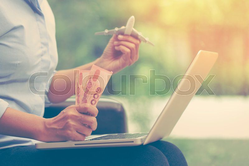 Young business woman using laptop computer and holding airplane with money. travel concept, stock photo