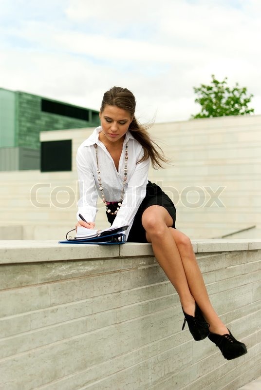 Beautiful Brunette Woman In Black Skirt And Jacket Sitting On Cube Stock Photo
