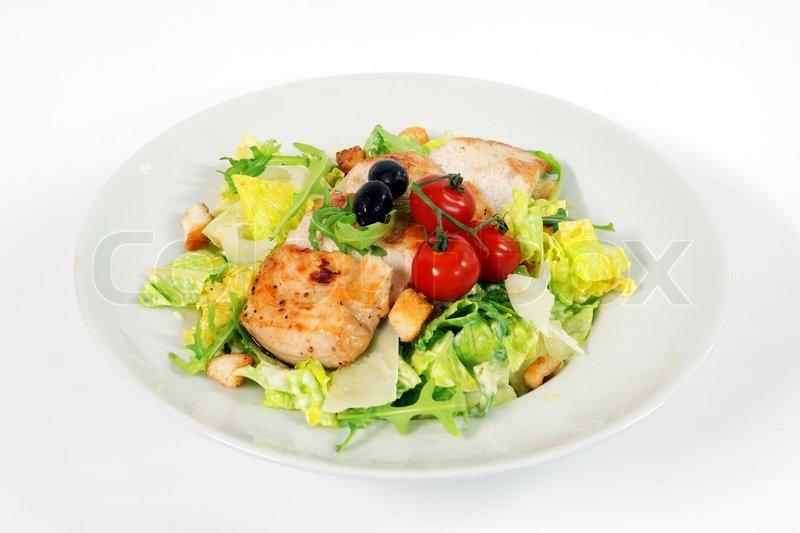 Stock image of caesar salad with chicken steak on white background