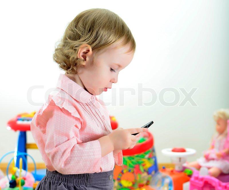 Kleine mädchen das mit handy im zimmer spielzeug